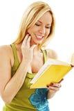 Muchacha hermosa que lee un libro y una sonrisa Fotografía de archivo libre de regalías