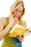 Muchacha hermosa que lee un libro y una sonrisa Fotos de archivo libres de regalías