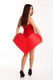 Muchacha hermosa que lleva a cabo el corazón de papel rojo Fotografía de archivo