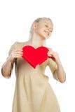 Muchacha hermosa que lleva a cabo el corazón en brazos Fotografía de archivo libre de regalías