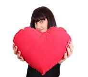 Muchacha hermosa que lleva a cabo el corazón rojo de la tarjeta del día de San Valentín Foto de archivo