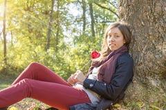 Muchacha hermosa que lleva a cabo el corazón rojo en un palillo mientras que se sienta en Imagen de archivo