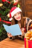 Muchacha hermosa que lleva a cabo la enhorabuena del Año Nuevo y de la Navidad Fotografía de archivo libre de regalías