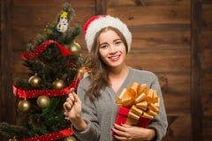 Muchacha hermosa que lleva a cabo un presente y una luz de Bengala cerca de árbol del Año Nuevo Foto de archivo libre de regalías