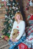 Muchacha hermosa que lleva a cabo un regalo de Navidad delante de ella Fotos de archivo libres de regalías