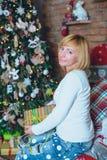 Muchacha hermosa que lleva a cabo un regalo de Navidad delante de ella Imagenes de archivo