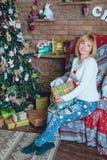 Muchacha hermosa que lleva a cabo un regalo de Navidad delante de ella Imágenes de archivo libres de regalías