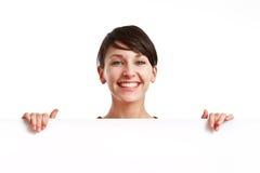 Muchacha hermosa que lleva a cabo a una tarjeta blanca vacía Imagen de archivo libre de regalías