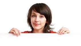 Muchacha hermosa que lleva a cabo a una tarjeta blanca vacía Fotos de archivo libres de regalías