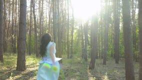 Muchacha hermosa que lleva el vestido azul y que sostiene la manzana, corriendo en el bosque almacen de video