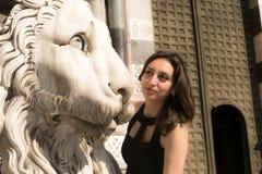 Muchacha hermosa que lleva un vestido negro al lado de la estatua gótica del león del estilo Foto de archivo