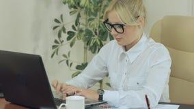 Muchacha hermosa que mecanografía en un teclado en oficina metrajes