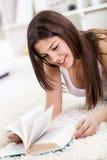 Muchacha hermosa que miente en el suelo que lee un libro Imagen de archivo libre de regalías