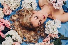 Muchacha hermosa que miente en flores Fotos de archivo