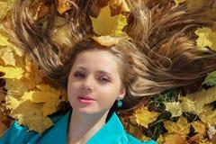 Muchacha hermosa que miente en hierba con las hojas de arce en otoño imagen de archivo