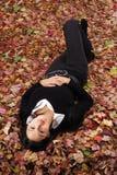 Muchacha hermosa que miente en hojas de otoño Fotos de archivo libres de regalías