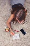 Muchacha hermosa que miente en la alfombra en casa y que escribe en un cuaderno al lado de su taza de té con el soporte del limón Fotografía de archivo
