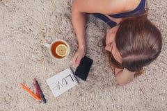 Muchacha hermosa que miente en la alfombra en casa y que lee SMS, al lado de su taza de té con el soporte del limón, visión super Imagen de archivo