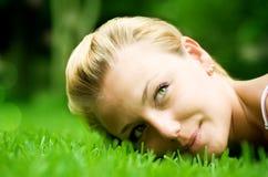 Muchacha hermosa que miente en la hierba imagen de archivo