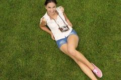 Muchacha hermosa que miente en la hierba Fotografía de archivo