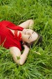 Muchacha hermosa que miente en la hierba Fotografía de archivo libre de regalías
