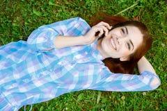 Muchacha hermosa que miente en la hierba con su teléfono Fotos de archivo libres de regalías
