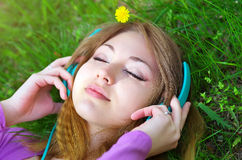 Muchacha hermosa que miente en la hierba y la música que escucha Fotos de archivo libres de regalías