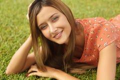 Muchacha hermosa que miente en la hierba y que sonríe mientras que mira la cámara Fotografía de archivo libre de regalías