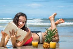 Muchacha hermosa que miente en la playa que lee un libro con el summ fresco Imagen de archivo libre de regalías