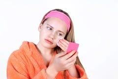 Muchacha hermosa que mira en el espejo que aplica un cojín de algodón Imagen de archivo libre de regalías