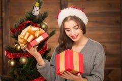 Muchacha hermosa que mira en una caja de actual árbol cercano del Año Nuevo Fotos de archivo libres de regalías