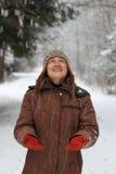 Muchacha hermosa que mira la nieve que cae Imagen de archivo