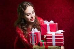 Muchacha hermosa que mira los regalos Fotografía de archivo libre de regalías