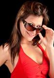 Muchacha hermosa que mira sobre las gafas de sol Imágenes de archivo libres de regalías