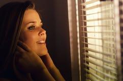 Muchacha hermosa que mira a través de la ventana Foto de archivo libre de regalías