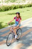 Muchacha hermosa que monta una bicicleta en el parque de la ciudad Fotografía de archivo