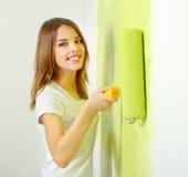 Muchacha hermosa que pinta una pared Imagen de archivo libre de regalías