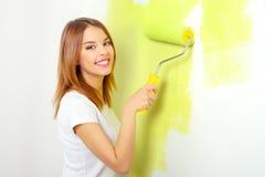 Muchacha hermosa que pinta una pared Imágenes de archivo libres de regalías