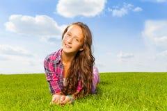 Muchacha hermosa que pone en hierba verde y la sonrisa Foto de archivo