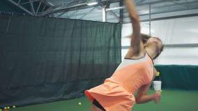 Muchacha hermosa que practica sirviendo la bola en tenis almacen de metraje de vídeo
