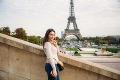 Muchacha hermosa que presenta al fotógrafo contra la perspectiva de la torre Eiffel Photosession del otoño tiempo soleado imagen de archivo