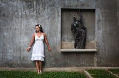 Muchacha hermosa que presenta cerca de la estatua una mujer en un estilo del desván muchacha que presenta en sitio fotos de archivo libres de regalías