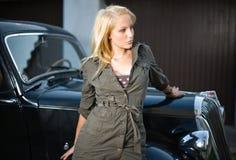 Muchacha hermosa que presenta con el coche negro de la vendimia. Imagen de archivo