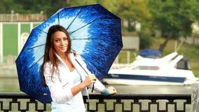 Muchacha hermosa que presenta con el paraguas. metrajes