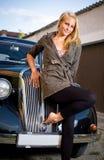 Muchacha hermosa que presenta con un coche negro de la vendimia. Fotografía de archivo