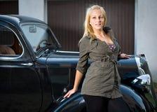 Muchacha hermosa que presenta con un coche negro de la vendimia. Foto de archivo