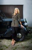 Muchacha hermosa que presenta con un coche negro de la vendimia. Foto de archivo libre de regalías