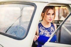 Muchacha hermosa que presenta en el coche retro blanco en el tejado imagen de archivo libre de regalías