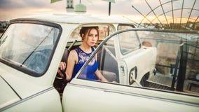 Muchacha hermosa que presenta en el coche retro blanco en el tejado fotografía de archivo