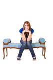 Muchacha hermosa que presenta en el sofá antiguo Foto de archivo libre de regalías
